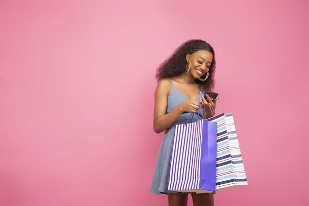 いくつかの買い物袋を持って幸せを感じているかわいいアフリカ系アメリカ人の女の子のクローズアップショット