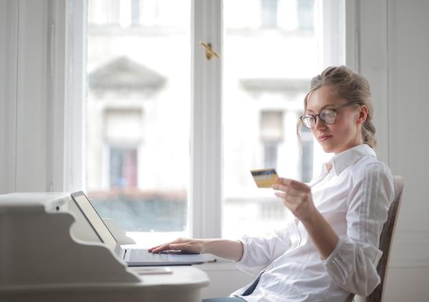노트북으로 작업하고 그녀의 카드를보고 흰 셔츠와 예쁜 여성의 근접 촬영 샷