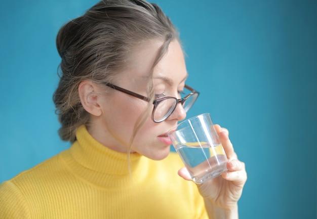 黄色のトップ飲料水ときれいな女性のクローズアップショット