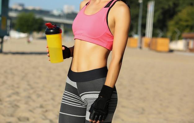 ビーチでポーズをとって水筒を持って、スポーツフォームを持つきれいな女性のクローズアップショット。テキスト用のスペース