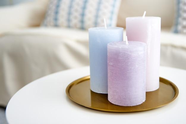 방 장식으로 흰색 테이블에 보라색과 파란색 촛불의 근접 촬영