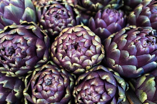 Снимок фиолетовых артишоков, аккуратно сложенных на рынке крупным планом