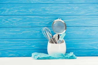 Closeup shot of rag, pastry brush, whisk and sieve in front of blue wooden wall