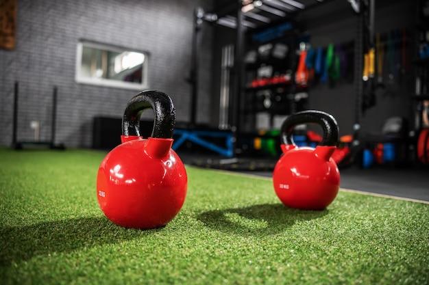 緑の人工芝屋内ジムでトレーニングするための赤い2つのケトルベルのクローズアップショット