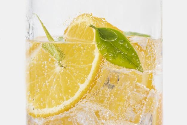 Снимок освежающего напитка с апельсиновыми и зелеными листьями крупным планом
