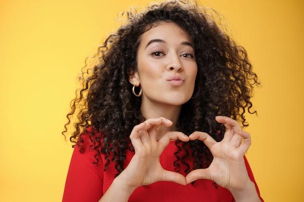 キスやmwahshで巻き毛の折り畳み唇を持つロマンチックで優しい若いガールフレンドのクローズアップショット...