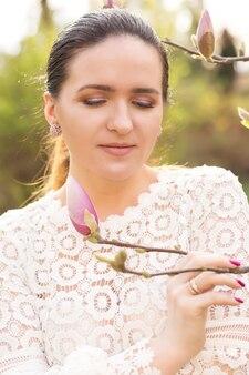 咲くモクレンの花の近くでポーズをとってヌードメイクでロマンチックなブルネットモデルのクローズアップショット