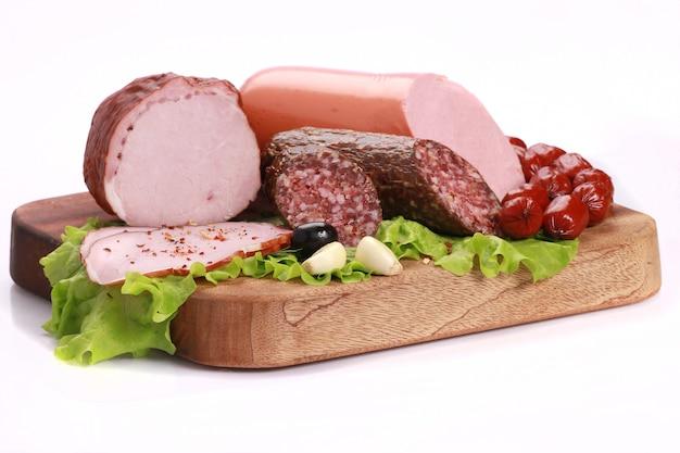 Крупным планом снимок ломтиков колбасы с зеленым салатом на деревянной доске