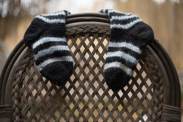 Снимок крупным планом полосатых носков, висящих на спинке стула