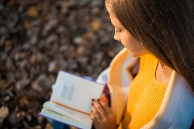가을 공원에서 책을 읽는 10대 소녀의 근접 촬영 샷