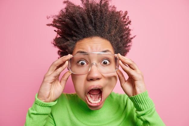 겁에 질린 감정적 인 아프리카 계 미국인 여자의 근접 촬영 샷은 도청 된 눈과 넓은 입을 쳐다 본다.