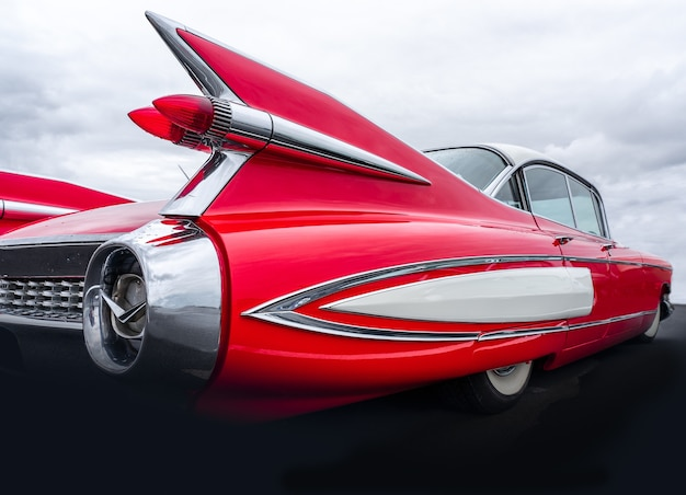 Снимок крупным планом задней части красной машины под небом, полным облаков