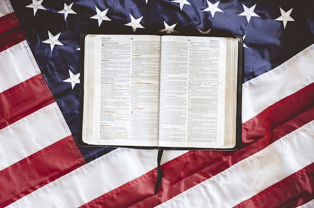 アメリカの国旗を掲げたページで開かれた聖書のクローズアップショット-祈りのコンセプトに最適
