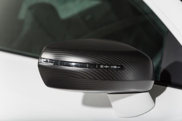 Снимок крупным планом черного бокового зеркала современного белого автомобиля