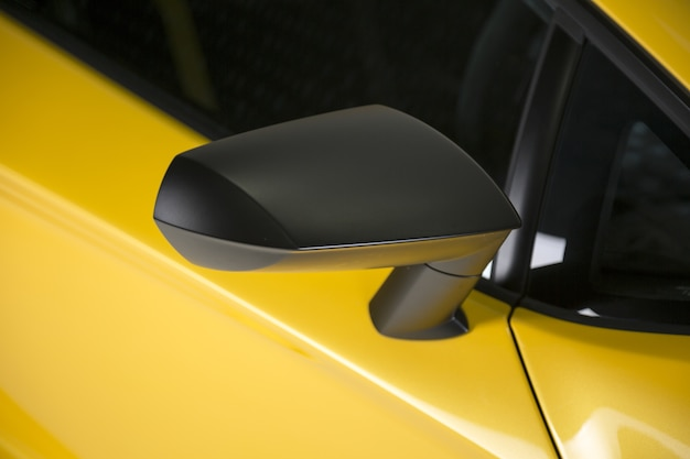 Снимок крупным планом черного бокового зеркала желтого современного спортивного автомобиля