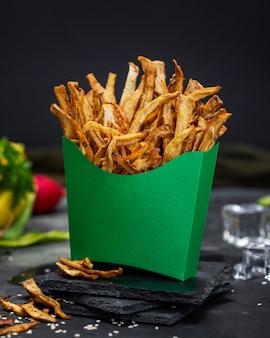 Снимок обезвоженного сладкого картофеля в коробке из зеленой бумаги крупным планом