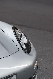 白いスポーツカーの左ヘッドライトのクローズアップショット