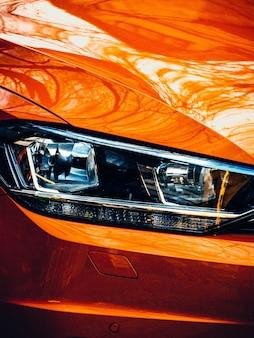 Снимок крупным планом правой фары оранжевого современного автомобиля