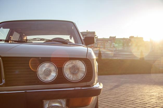 日没時に白いヴィンテージクラシックカーの丸いヘッドライトのクローズアップショット