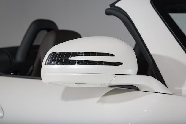 현대 흰색 쿠페 형 자동차의 사이드 미러의 근접 촬영 샷