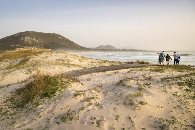 화창한 날에 라리노 해변으로 걸어가는 관광객들의 클로즈업 샷