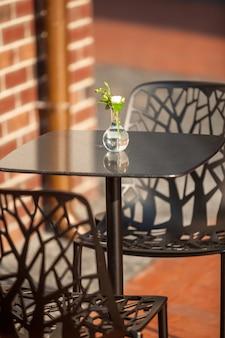 야외 카페에서 테이블에 서있는 꽃병에 흰 꽃의 근접 촬영 샷