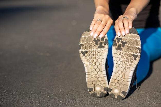 スタジアムでのトレーニングの前にストレッチする女性の足のクローズアップショット。テキスト用のスペース