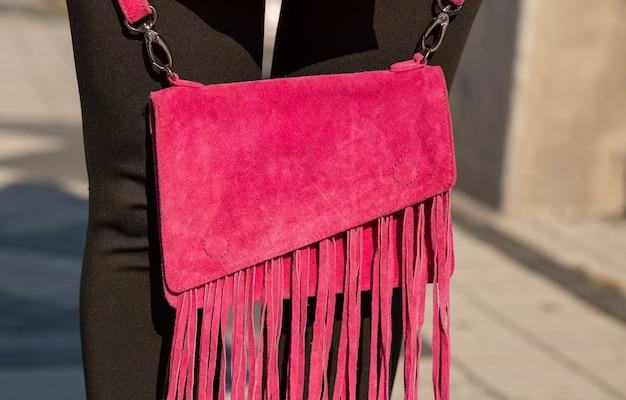 小さなスエードの財布を持っている女性のクローズアップショット。アウトドアショット