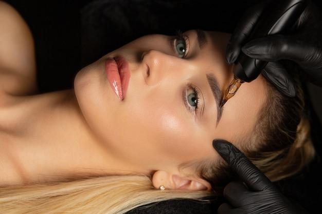 Крупным планом снимок женщины в перчатках, делающей перманентный макияж бровей молодой блондинке в косметологическом салоне