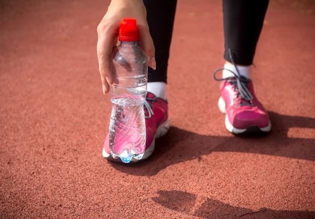 ランニング トラックで水のペットボトルを保持している女性ランナーのクローズ アップ ショット