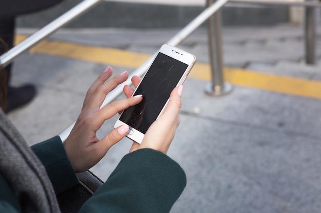 壊れた画面で携帯電話を持っている女性の手のクローズアップショット