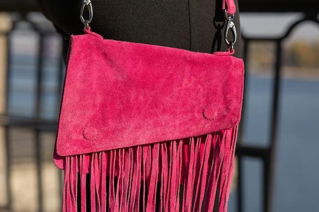 小さなスエードの財布を身に着けている女性のクローズアップショット。アウトドアショット