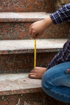 石段の高さを測定する労働者のクローズアップショット
