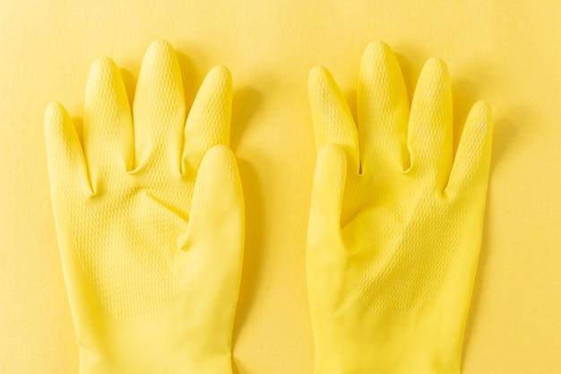 黄色の表面に黄色のプラスチック手袋のクローズアップショット