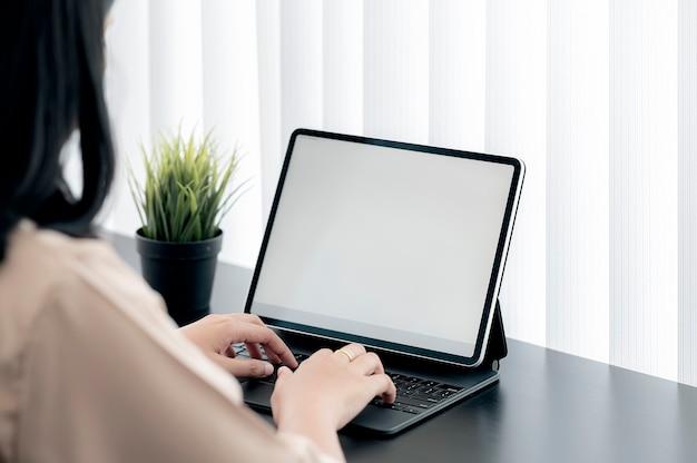 Крупным планом выстрелил молодых женских рук, набрав на клавиатуре планшета, сидя за столом в современном офисе.