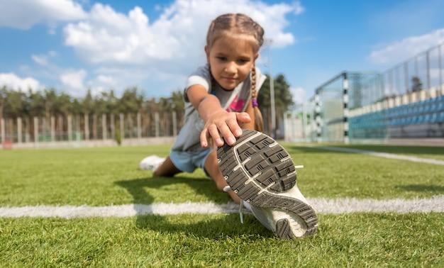 Снимок крупным планом молодой девушки, растягивая ноги на футбольном поле в солнечный день
