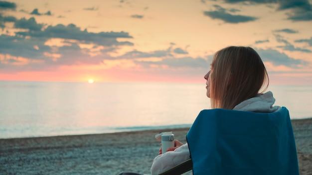 魔法瓶から飲んで、ビーチでキャンプチェアに座っている若い女性のクローズアップショット