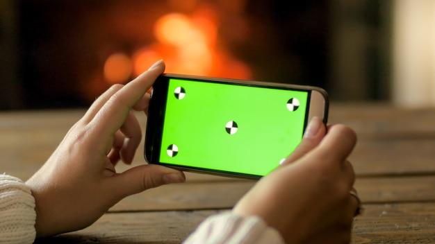 불타는 벽난로에서 빈 녹색 화면으로 스마트폰을 들고 젊은 여자의 근접 촬영 샷. 이미지 또는 디자인을 위한 장소