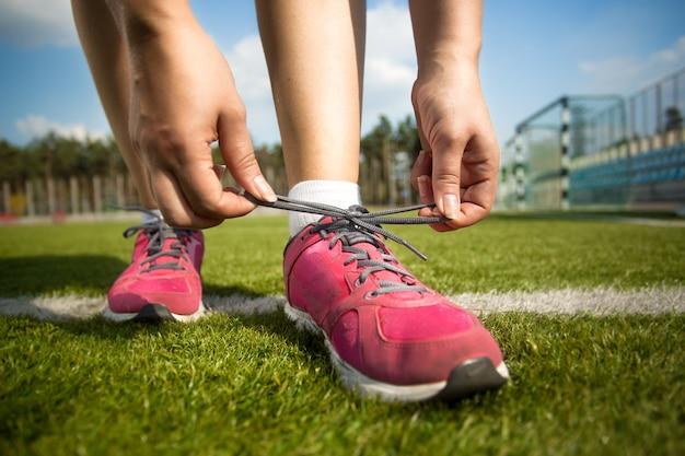 走る前に靴ひもを結ぶ若い女性のクローズアップショット