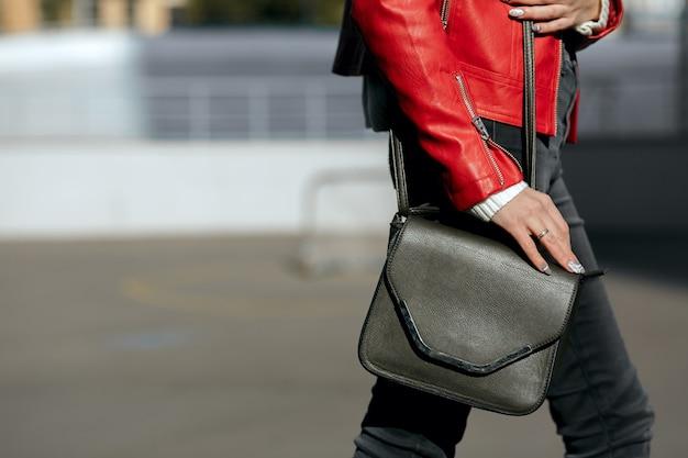黒革の女性の財布と歩く若い女性のクローズアップショット