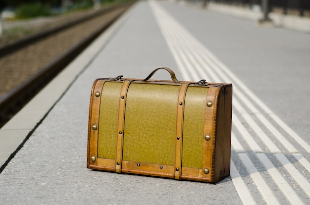 Closeup shot of an old brown suitcase on railroad station in switzerland