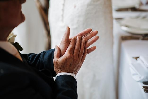 Colpo del primo piano di un applauso di mani maschio anziano