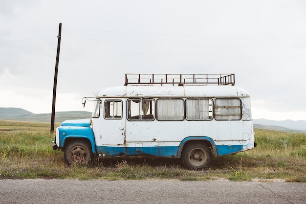 Closeup shot of an old minibus on a green landscape under a cloudy sky