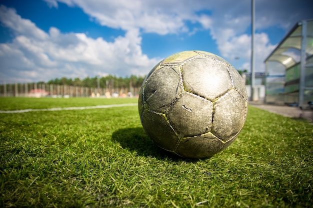 Closeup shot of old soccer ball on grass field at sunny day