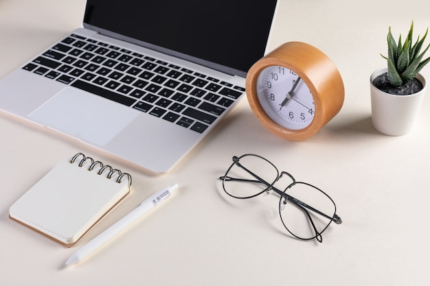 Closeup shot of an open laptop, glasses, notepad, pen, a clock, and a plant
