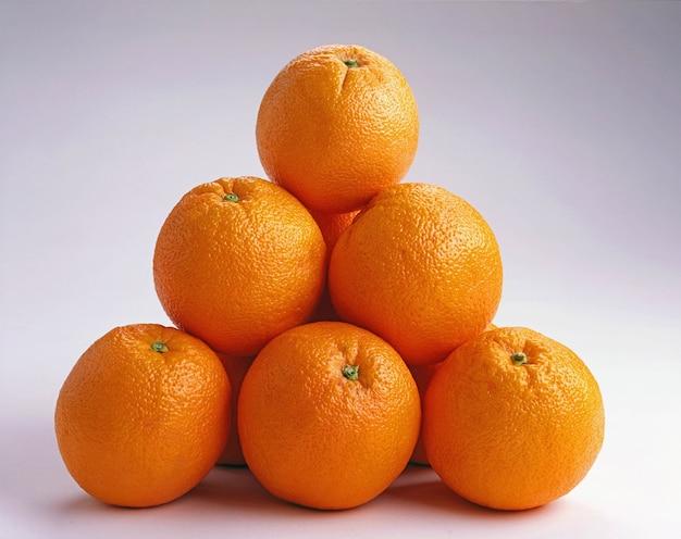 Colpo del primo piano di arance uno sopra l'altro su una superficie bianca - ottimo per uno sfondo