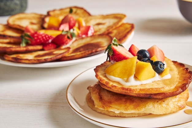Closeup shot of pancakes with fruits on the top at breakfast