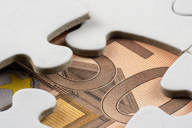 Closeup shot of a part of money seen under a removed piece of a jigsaw puzzle