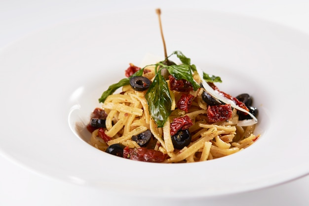 Closeup shot of pasta with dried fruits, olives, and mint on a white wall