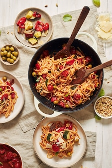 Closeup shot of pasta with vegetables and ingredients on a white table